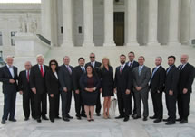 A group of professionally-dressed men and women standing in front of a white government building