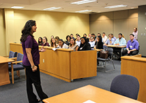 Woman standing and speaking to a group of seated students in a mock courtroom