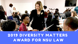 "Professor listening to a student speak in the classroom, with a banner stating ""2019 Diversity Matters Award For NSU Law"""
