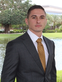 Portrait of a student in a suit and golden brown tie standing outside with a lake in the background